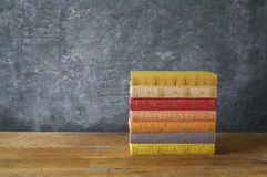 Colorful books in front of a black board royalty free stock photography