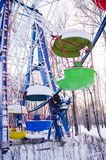 Colorful booths of ferris wheel under the snow. Closed for the winter. vertical Stock Image