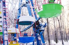 Colorful booths of ferris wheel under the snow. Closed for the winter Stock Image