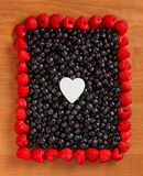 Colorful border frame made of berries. Colorful border frame made of sweet forest berries on the table Stock Photography