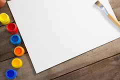 Colorful bottles, paintbrush and paper arranged on wooden surface Stock Image