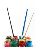 colorful of bottles poster color with three paintbrushes dipped Royalty Free Stock Photography