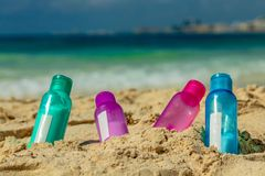 Colorful bottles in the sand royalty free stock image