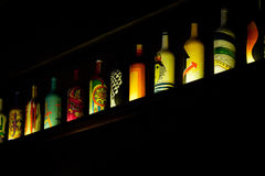 Colorful bottles stay on shelf in dark royalty free stock images