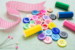 Colorful botton and thread on fabric Stock Photos