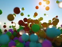 Colorful bouncing balls outdoors against blue sunny sky. Lots of colorful bouncing balls outdoors against blue sunny sky with chaotic motion - perfect party stock image