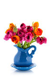 Colorful bouquet butter cups in blue vase Stock Photo