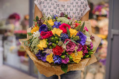 Colorful bouquet  with different flowers in hands Royalty Free Stock Images