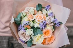Colorful bouquet of different fresh flowers in the hands of florist woman. Rustic flower background. Craft bouquet of. Colorful bouquet of different fresh stock images