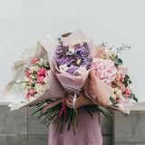 Colorful bouquet of different fresh flowers in the hands of florist woman. Rustic flower background. Craft bouquet of. Colorful bouquet of different fresh stock image