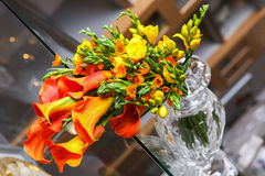 Colorful bouquet of orange calla lilies and other flowers on the table royalty free stock photo