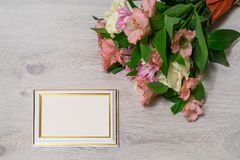 Colorful bouquet of roses, chrysanthemum and alstroemeria flower. S with empty photoframe on wooden background royalty free stock photo