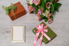 Colorful bouquet of roses, chrysanthemum and alstroemeria flower. S with gift boxes and empty photoframe on wooden background stock image