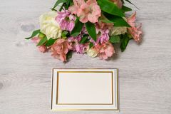 Colorful bouquet of roses, chrysanthemum and alstroemeria flower. S with empty photoframe on wooden background stock images