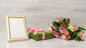 Colorful bouquet of roses, chrysanthemum and alstroemeria flower. S with gift box and empty photoframe on wooden background royalty free stock photo