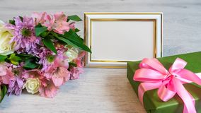 Colorful bouquet of roses, chrysanthemum and alstroemeria flower. S with gift box and empty photoframe on wooden background royalty free stock photos