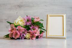 Colorful bouquet of roses, chrysanthemum and alstroemeria flower. S with gift box and empty photoframe on wooden background royalty free stock photography