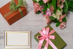 Colorful bouquet of roses, chrysanthemum and alstroemeria flower. S with gift boxes and empty photoframe on wooden background stock images