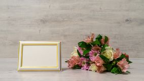 Colorful bouquet of roses, chrysanthemum and alstroemeria flower. S with empty photoframe on wooden background royalty free stock image