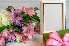 Colorful bouquet of roses, chrysanthemum and alstroemeria flowers. With gift box and empty photoframe on wooden background stock images