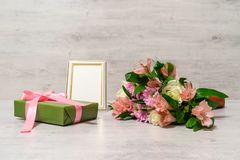 Colorful bouquet of roses, chrysanthemum and alstroemeria flower. S with gift box and empty photoframe on wooden background stock photography