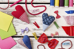 Colorful bow ties on table. Fabric hearts and blank papers. The workspace of a true artist Royalty Free Stock Photography