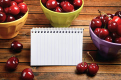 Colorful bowl with cherries and notepad Royalty Free Stock Photography