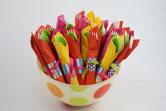 Colorful bowl with napkins. Colorful bowl full of plastic forks and spoons wrapped in colorful napkins Royalty Free Stock Images