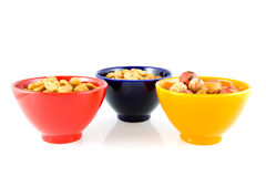 Colorful bowls with nuts. Isolated on white background royalty free stock image