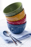 Colorful bowls. Stack of colorful bowls and spoons Stock Photos