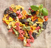 Colorful Bowtie Pasta Heart. Heart-shaped arrangement of colourfaul bowtie pastas, or farfalle, on rustic hessian material, concpetual of love and romance Stock Photography