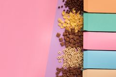 Colorful boxes with scattered cereals on pink background royalty free stock image