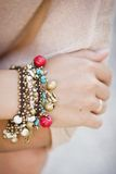 Colorful bracelet with shells and bells. On a girl's hand Stock Photo