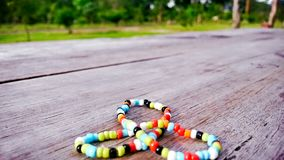Colorful bracelet on wood in triada. Colorful bracelet on wood outdoors Royalty Free Stock Image