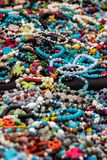 A colorful pile of jewelry at an outdoor marketplace. Colorful bracelets and necklaces lay on a table at an outdoor festival royalty free stock photography