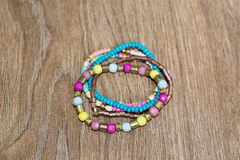 Colorful bracelets on a wooden background Royalty Free Stock Photos