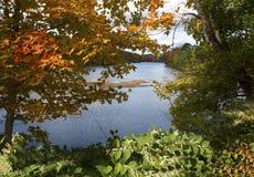Colorful branches frame the Farmington River in Canton, Connecti. Fall foliage on the Farmington River in the Collinsville section of Canton, Connecticut Stock Photo