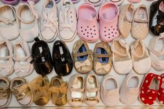 Colorful brand new baby girl shoes inside closet. With bright lighting stock photo