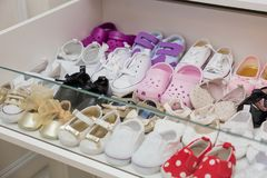 Colorful brand new baby girl shoes inside closet. With bright lighting royalty free stock photos