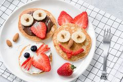 Colorful breakfast meal for kids. Pancake food art, funny animal faces made with fruits, nuts and chocolate spread. Concept of kids meal, kids breakfast, joy royalty free stock photography