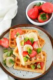 Colorful breakfast with waffles and fruits. Healthy breakfast table with belgian waffles, exotic fruits and coffee Royalty Free Stock Images