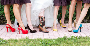 Colorful Bridesmaid's Shoes. Bride and bridesmaids showcase their shoes in a Texas wedding with the bride in cowgirl boots Royalty Free Stock Images