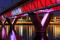 Colorful Bridge. Colorful light rail bridge across the river at sunset Stock Photos