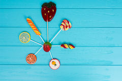 Colorful bright different lollipops on wooden turquoise board Royalty Free Stock Photography
