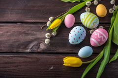 Colorful Easter eggs with yellow Tulip hand painted on a dark wooden background. Holiday spring card royalty free stock image