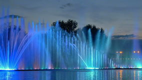 Colorful bright fountain with beautiful reflection. Amazing fantastic colorful fountain with bright illumination on the water pond or river with beautiful stock video footage