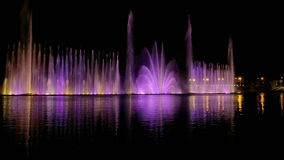 Colorful bright fountain with beautiful reflection. Amazing fantastic colorful fountain with bright illumination on the water pond or river with beautiful stock footage