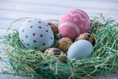 Colorful bright hand painted Easter eggs in a nest. Holiday spring card. Colorful bright hand painted Easter eggs in a nest on a blue background. Holiday spring Royalty Free Stock Image