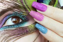 Colorful bright makeup on brown eye close-up. Color turquoise mascara.Peacock eye.Nail extension stock photo