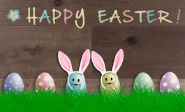 Colorful bright pastel easter eggs with bunny ears on wooden background, promotional sign with text happy easter Royalty Free Stock Photography